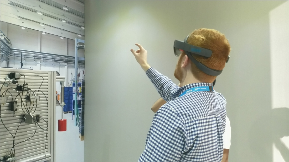 Matthew Champion wearing a HoloLens. He is reaching into the air with his index finger and thumb pinching in the air.
