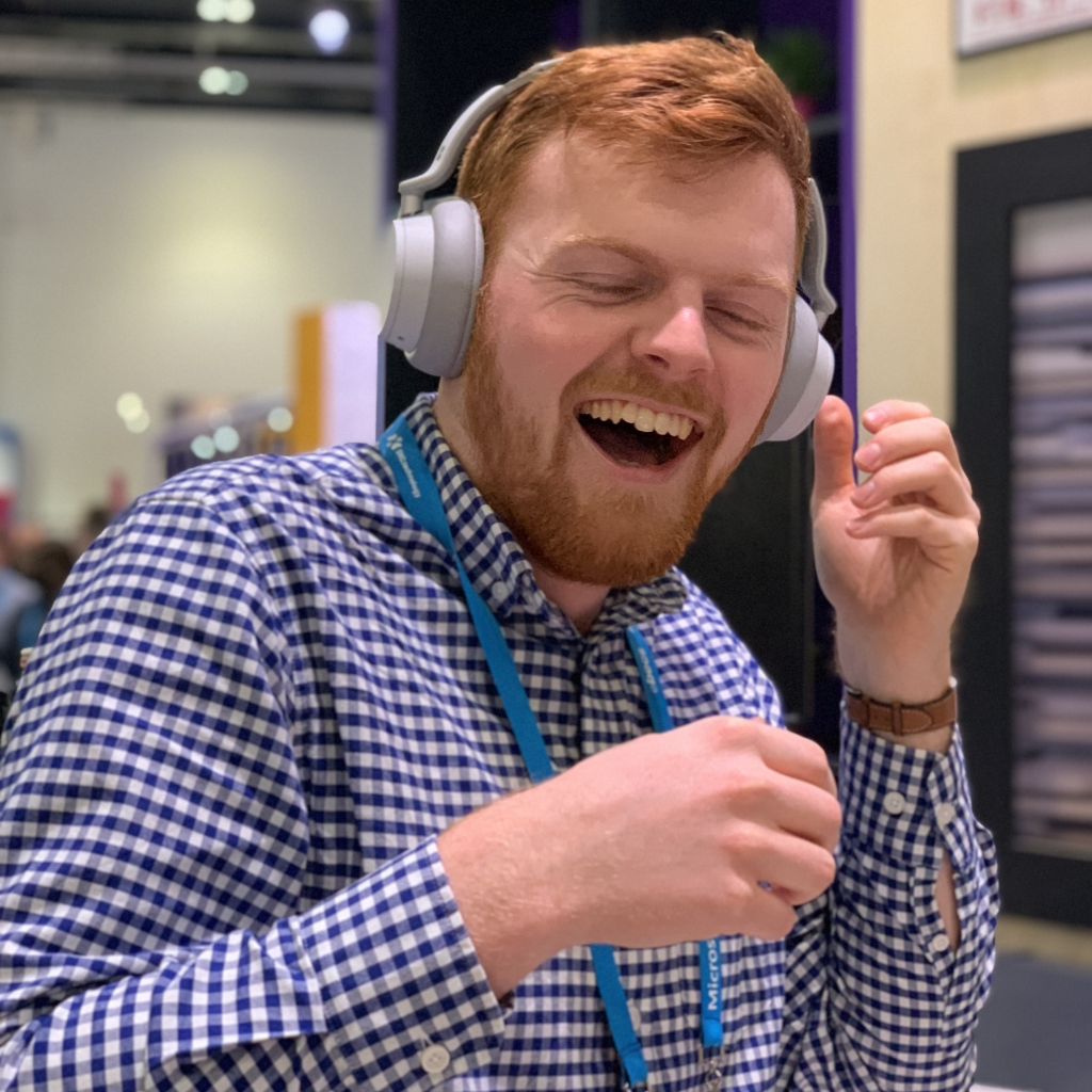 Matthew Champion laughing while listening to Surface headphones