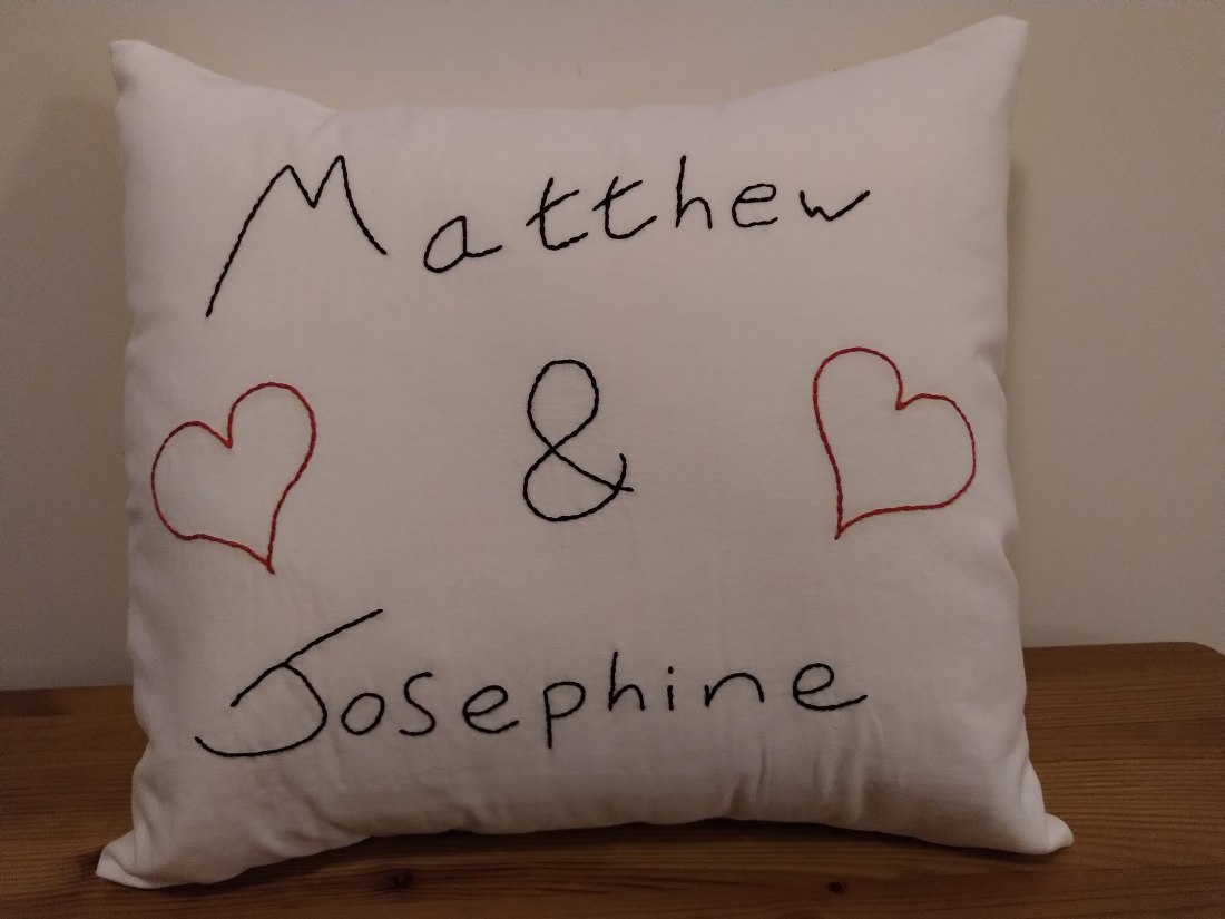 "A white square cushion with ""Matthew & Josephine"" embroidered on the front in black thread along with two hearts in red"