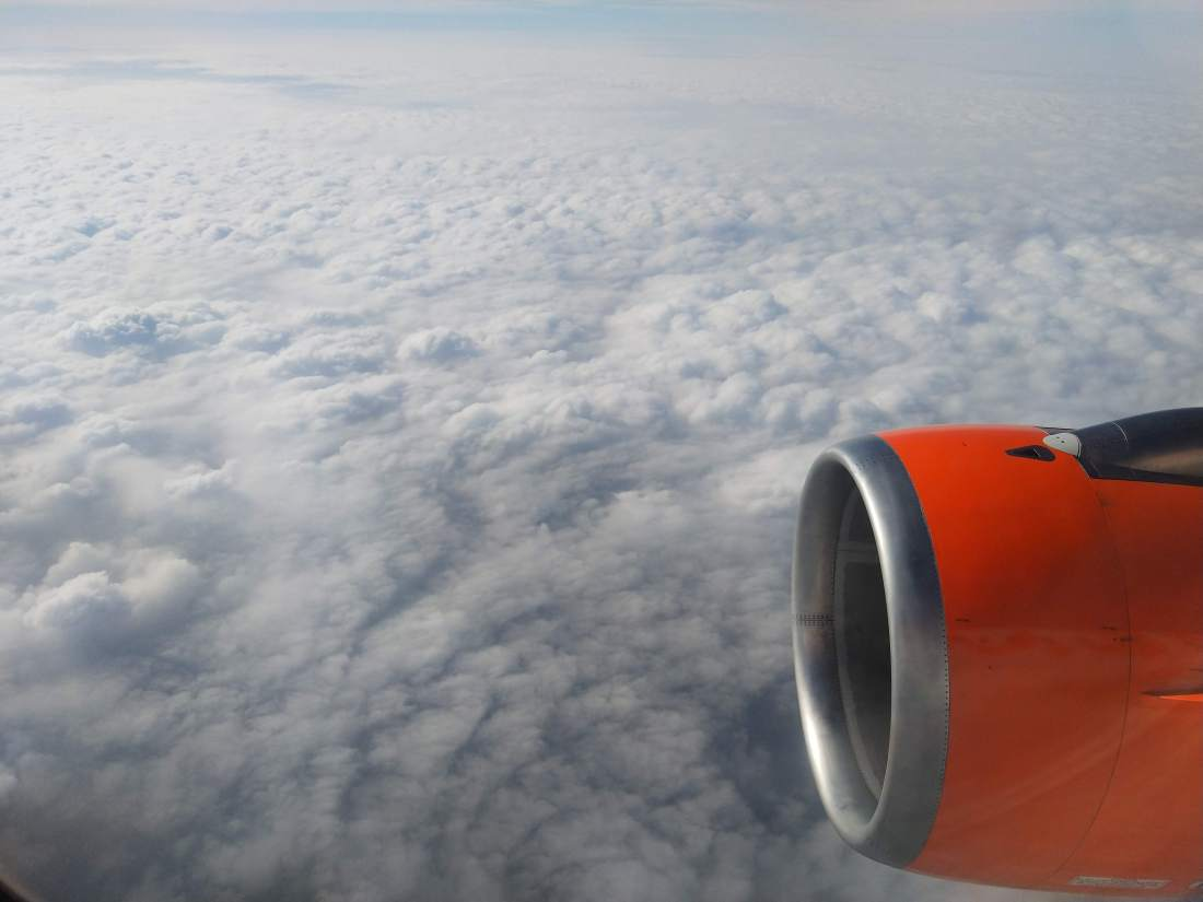 A photo taken from an aeroplane looking out the window. Clouds can be seen for miles and the front part of an aeroplane engine can be seen in the lower right