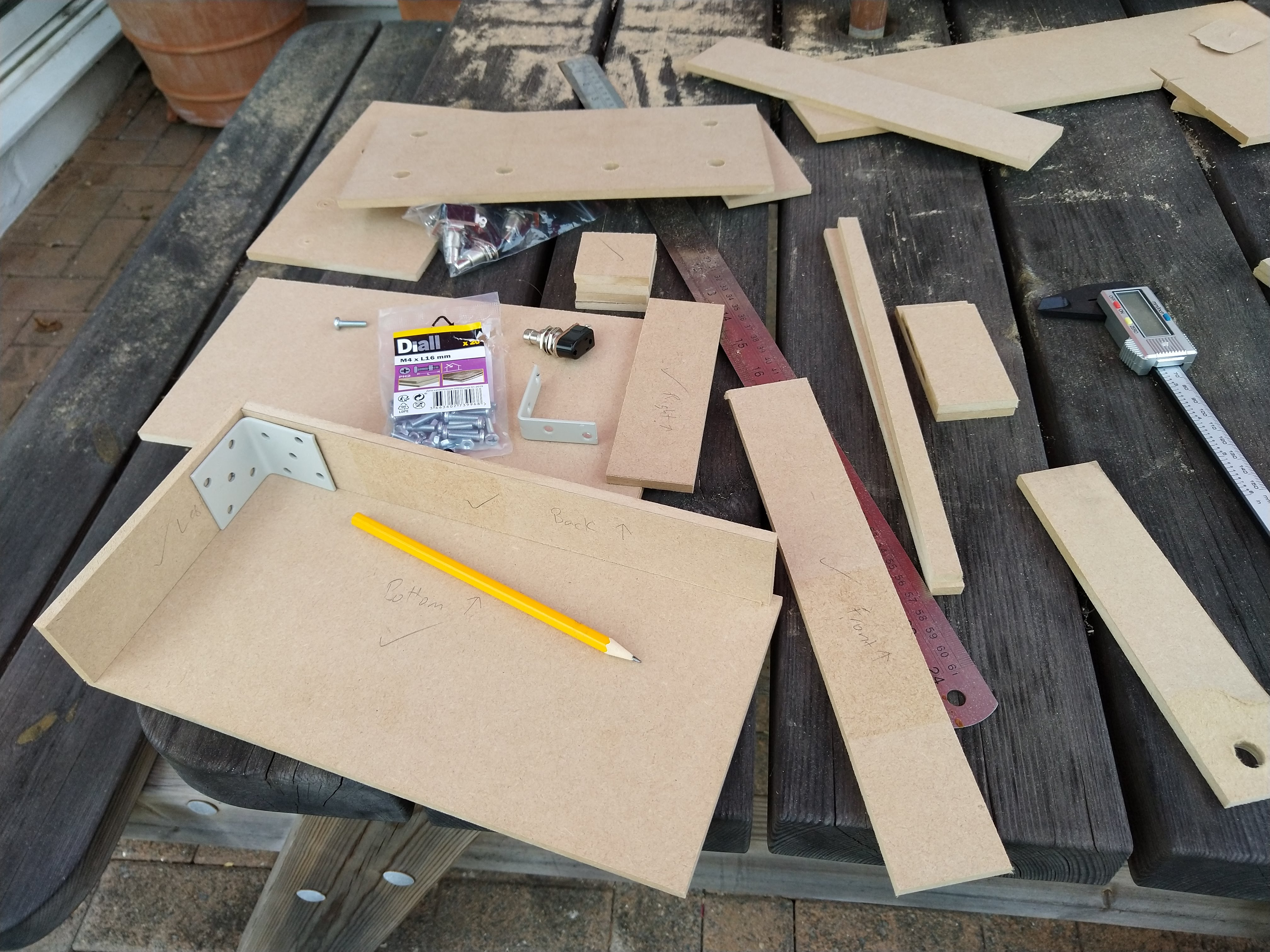 A table covered in MDF cut into various sizes. In the foreground there are pieces placed together into the start of a box shape, leaning against a corner bracket