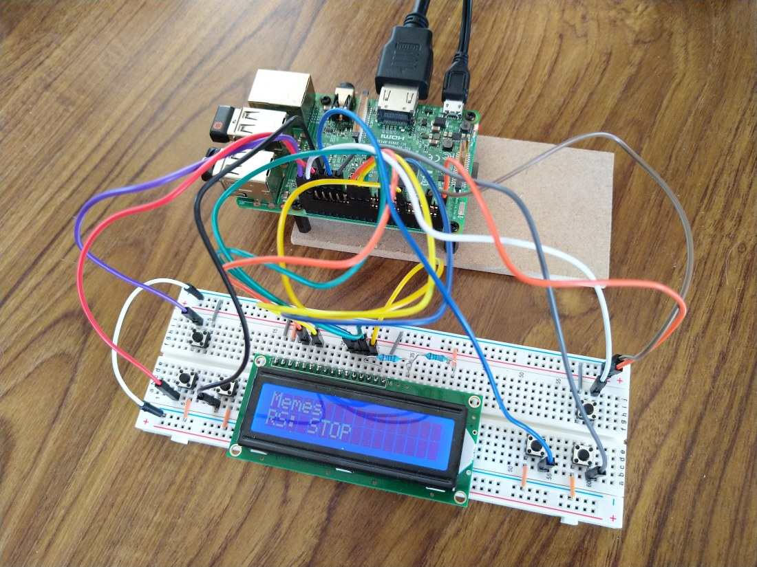 """A Raspberry Pi connected to a breadboard with various wires. The breadboard has a screen on it that says """"Memes"""" on the first row and """"RS: STOP"""" on the second"""