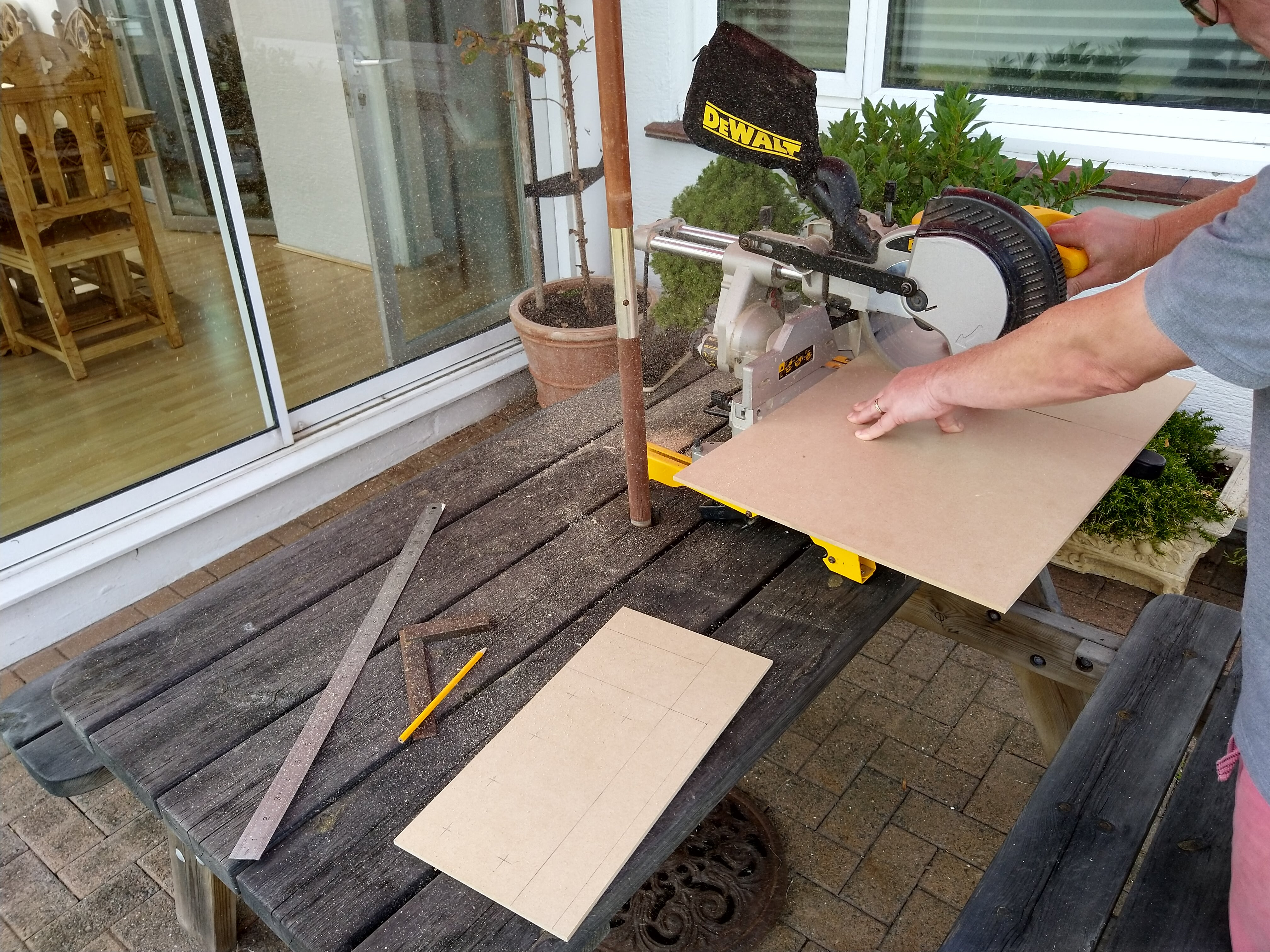 A DEWALT sliding mitre saw on an outside table being used to cut a sheet of MDF. There is a piece of MDF in the foreground with various lines drawn on it marking the cuts to make, along with a metal ruler, pencil and engineers square