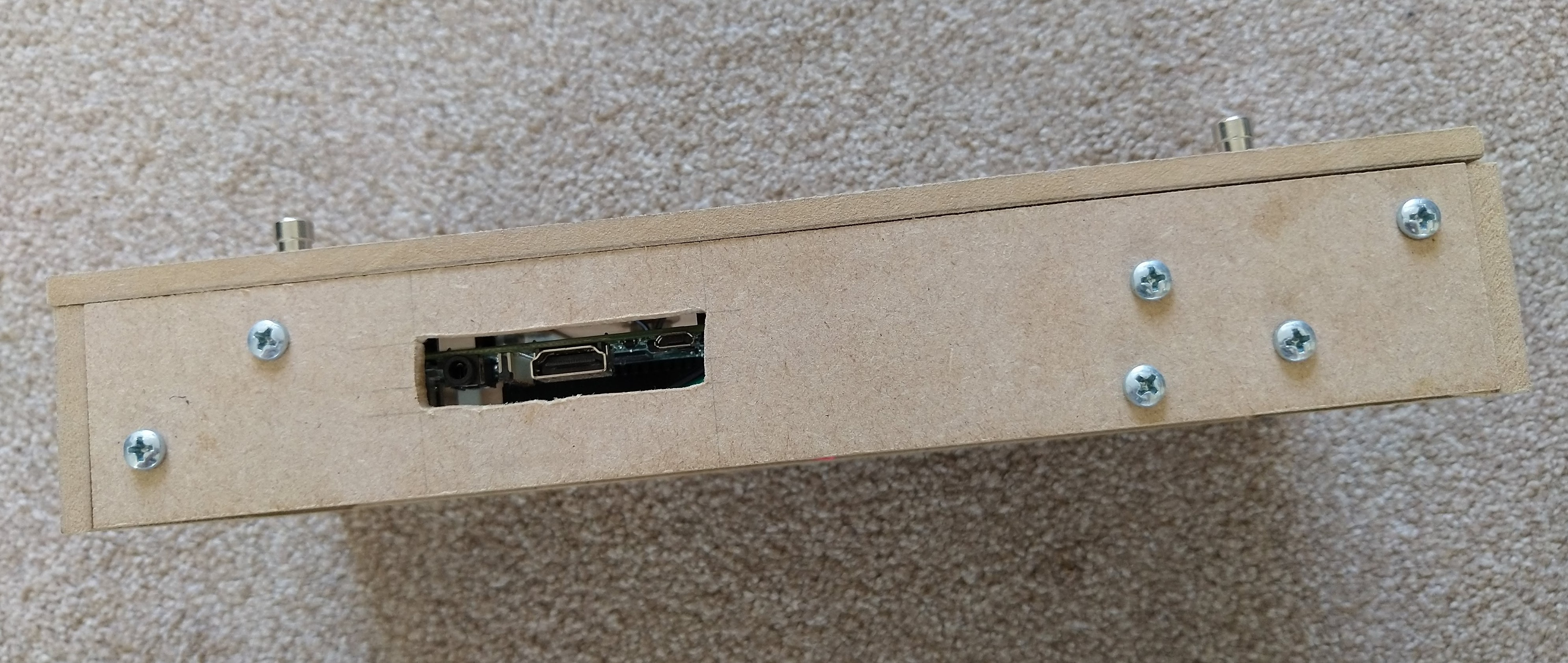 The back edge of the SoundFloored pedal. There are various cross-head screws visible along with a small rectangle cut out of the panel to make the 3.5mm, HDMI and power connections on an internal Raspberry Pi available