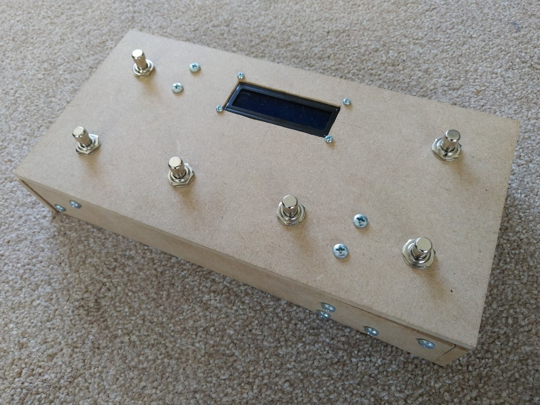 The top of the SoundFloored pedal. It is held together by various cross-head bolts and has six footswitches embedded in the top, with four along the close long edge and two along the far long edge (with a screen embedded in the lid between them)