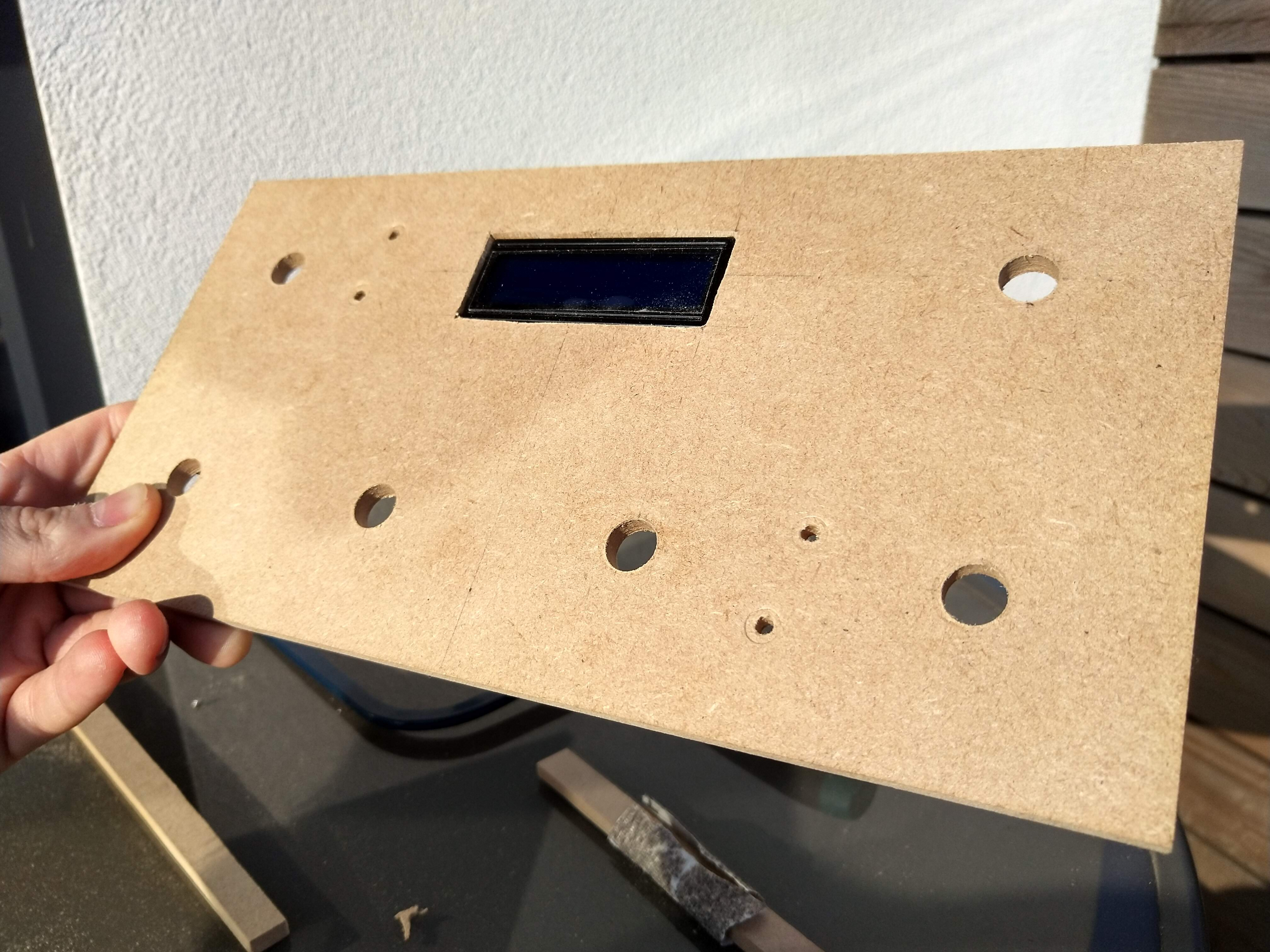 A piece of MDF with six holes in the top of it, with four along the lower long edge and two spaced against the upper long edge. There is an LCD screen in the middle of the upper long edge between the two holes