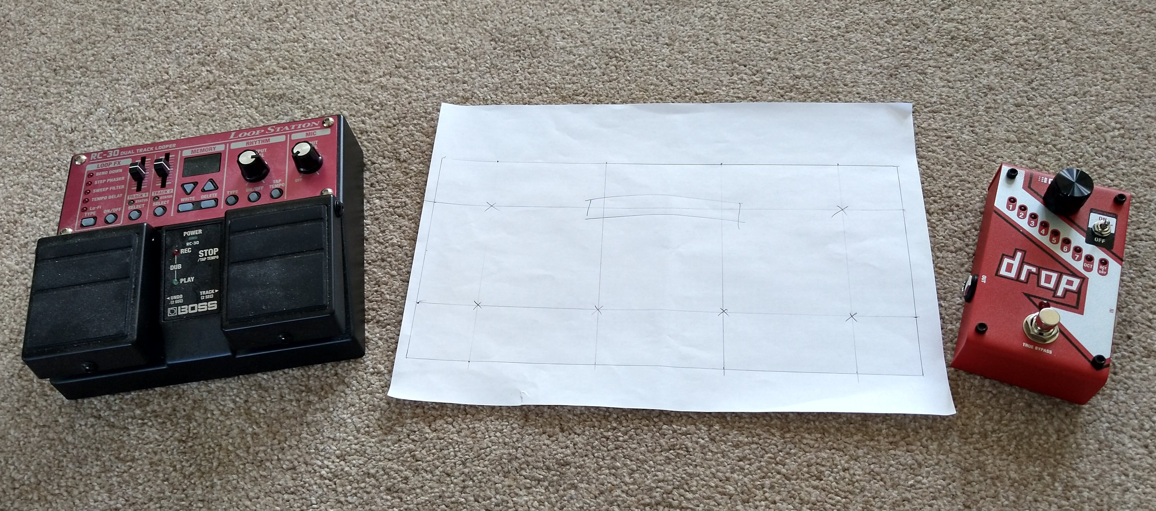 A sheet of paper on the floor with a 1:1 scale drawing of SoundFloored on it. To the left of the sheet of paper is a BOSS RC-30 pedal and to the right is a DigiTech Drop pedal