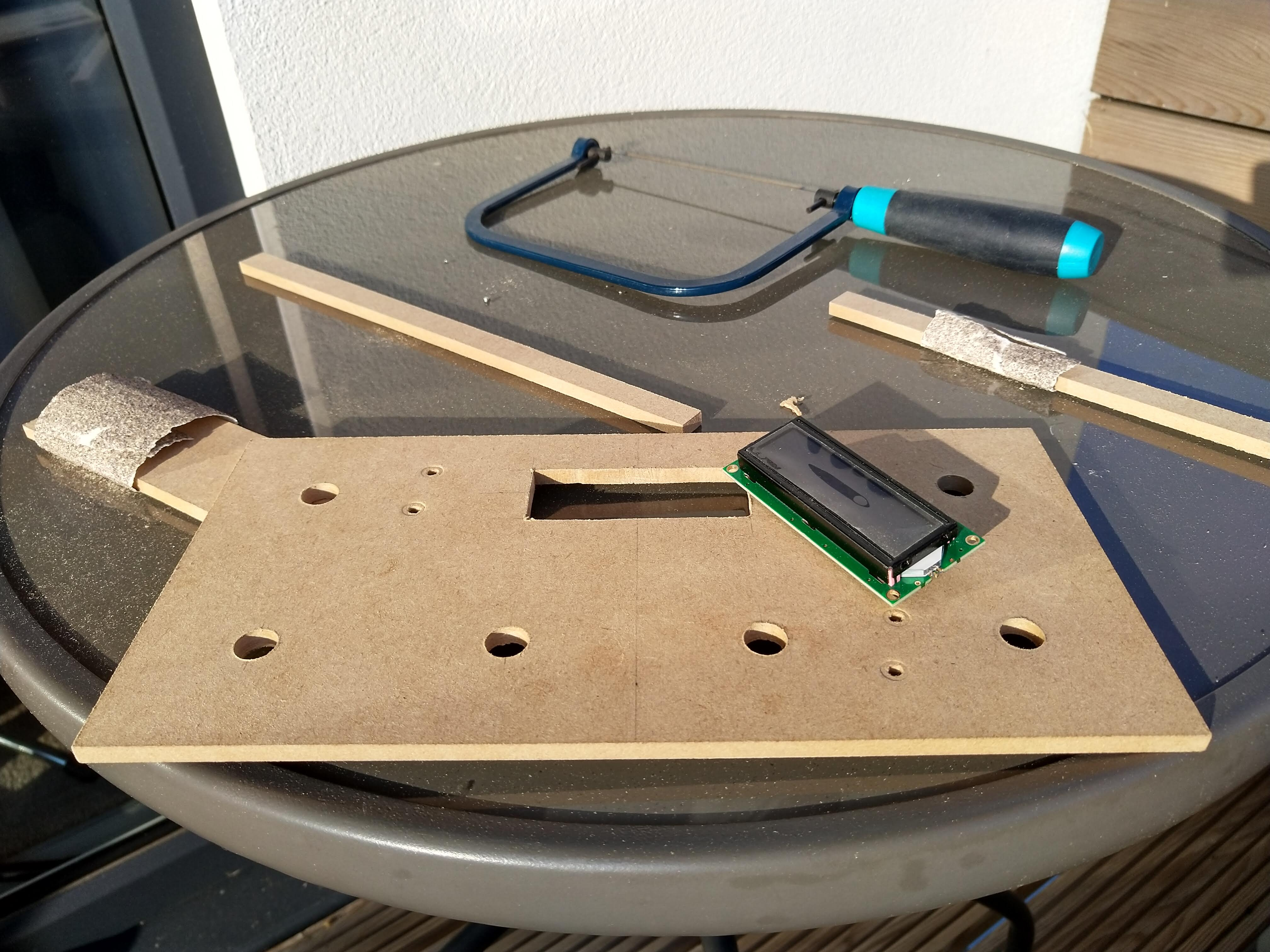 A piece of MDF with various holes cut out of it sitting on top of an outside table. In the background is a coping saw and smaller pieces of MDF with sandpaper wrapped around them. A small LCD screen sits on top of the largest piece