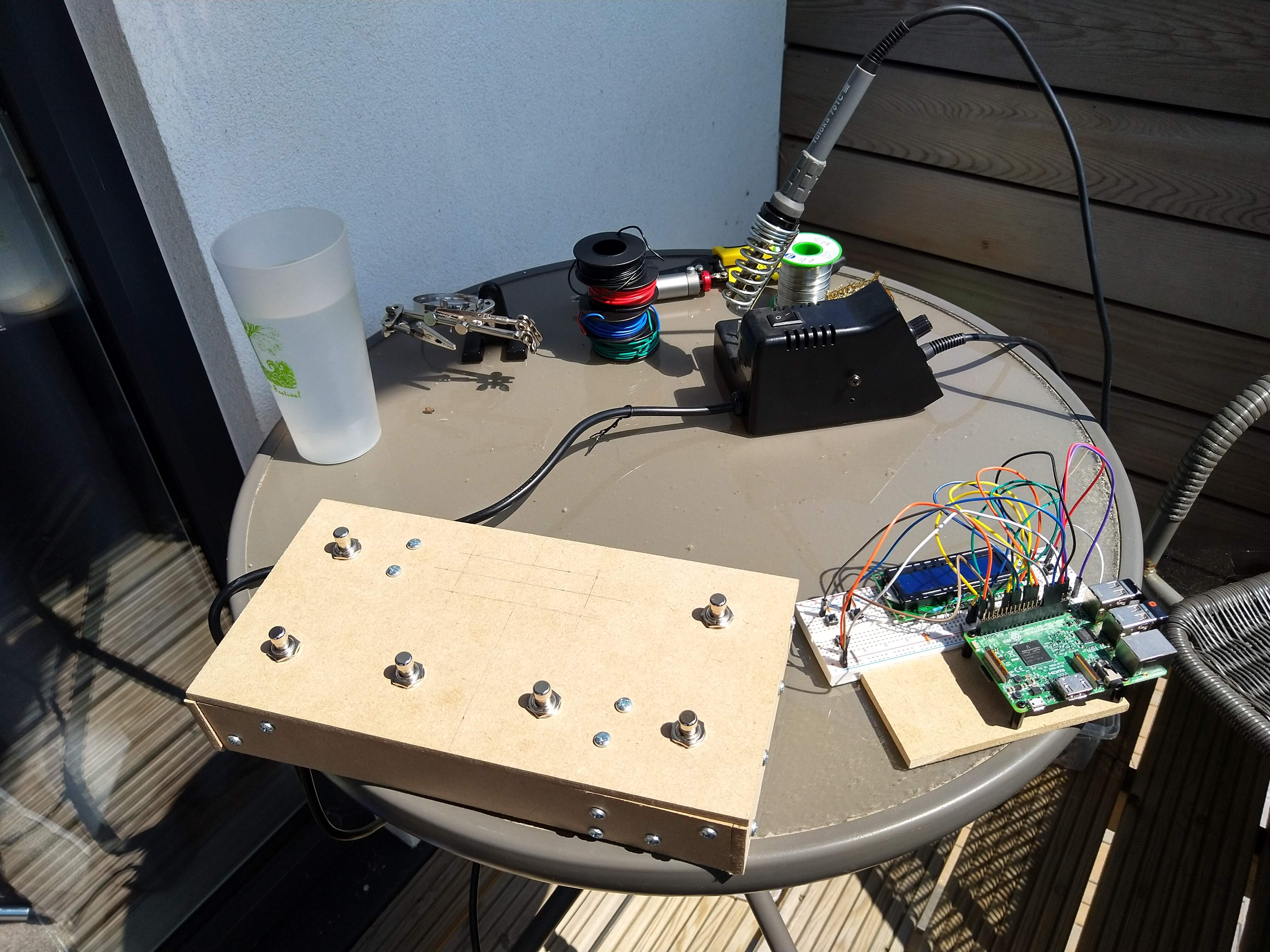 An outside table with the initial SoundFloored pedal box, the breadboard implementation and a soldering iron on it