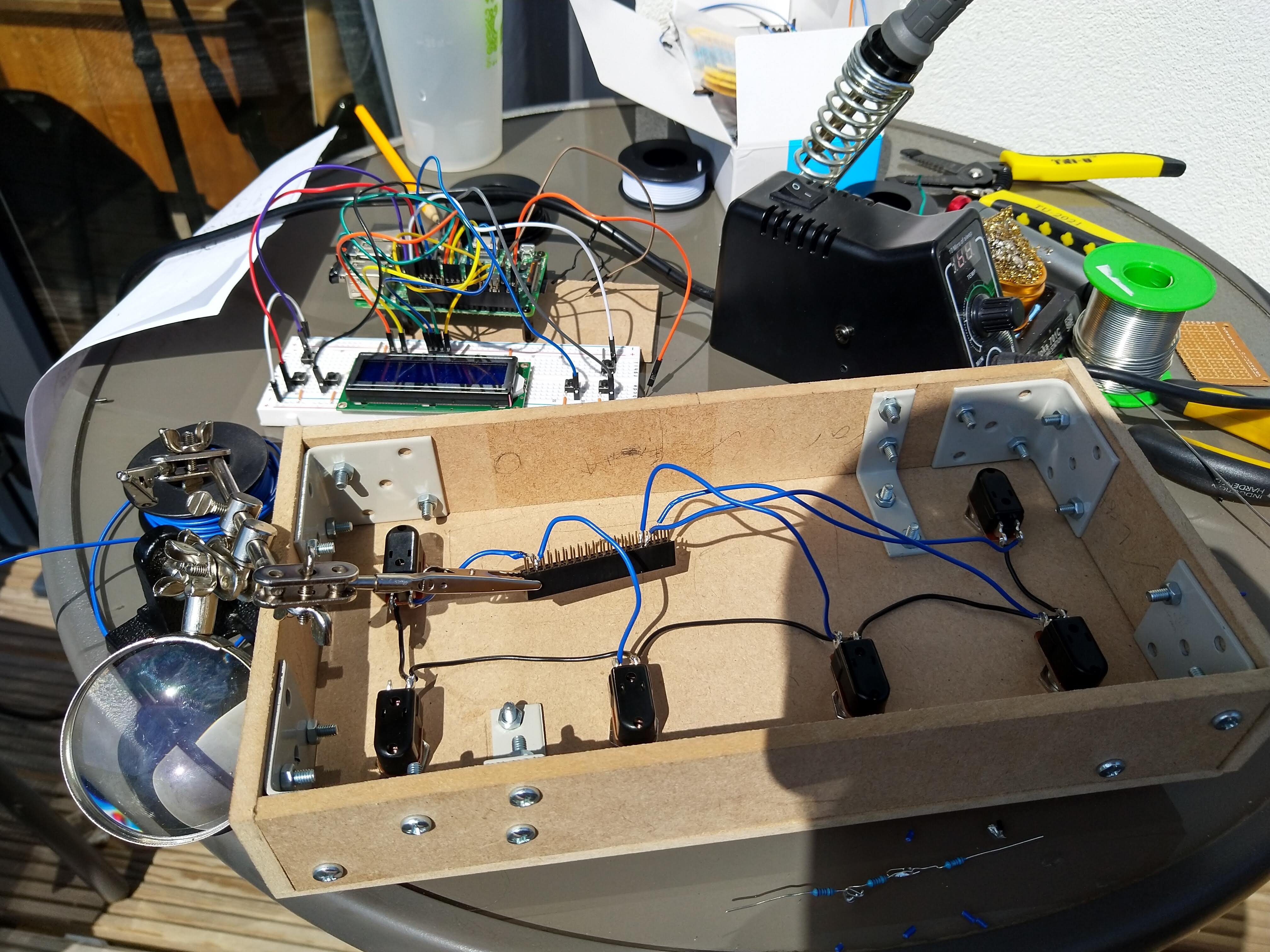 An outside table with the initial SoundFloored pedal box, the breadboard implementation and a soldering iron on it. The MDF box is upside down and a helping hand is holding a Raspberry Pi header extender that is being soldered to wires connecting it to various footswitches