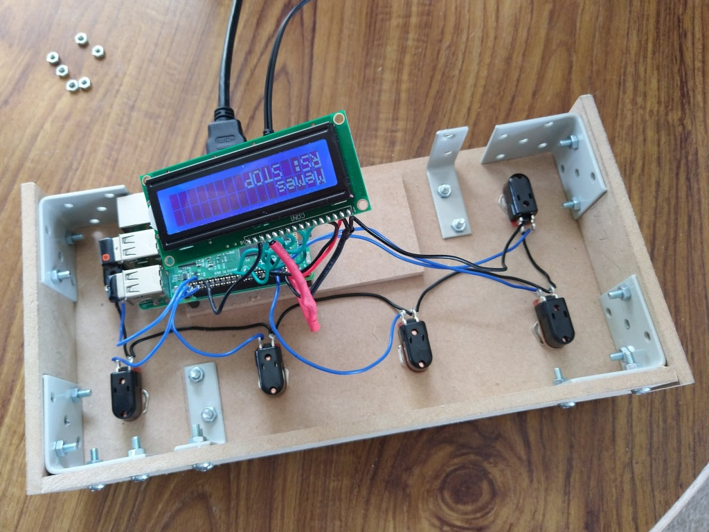 """The underside of the SoundFloored pedal that has a number of brackets holding it together and footswitches mounted into the lid. A Raspberry Pi is connected by wires to the footswitches and a small LCD screen, which is upside down (to the viewer) and displaying """"Memes"""" on the first row and """"RS: STOP"""" on the second"""