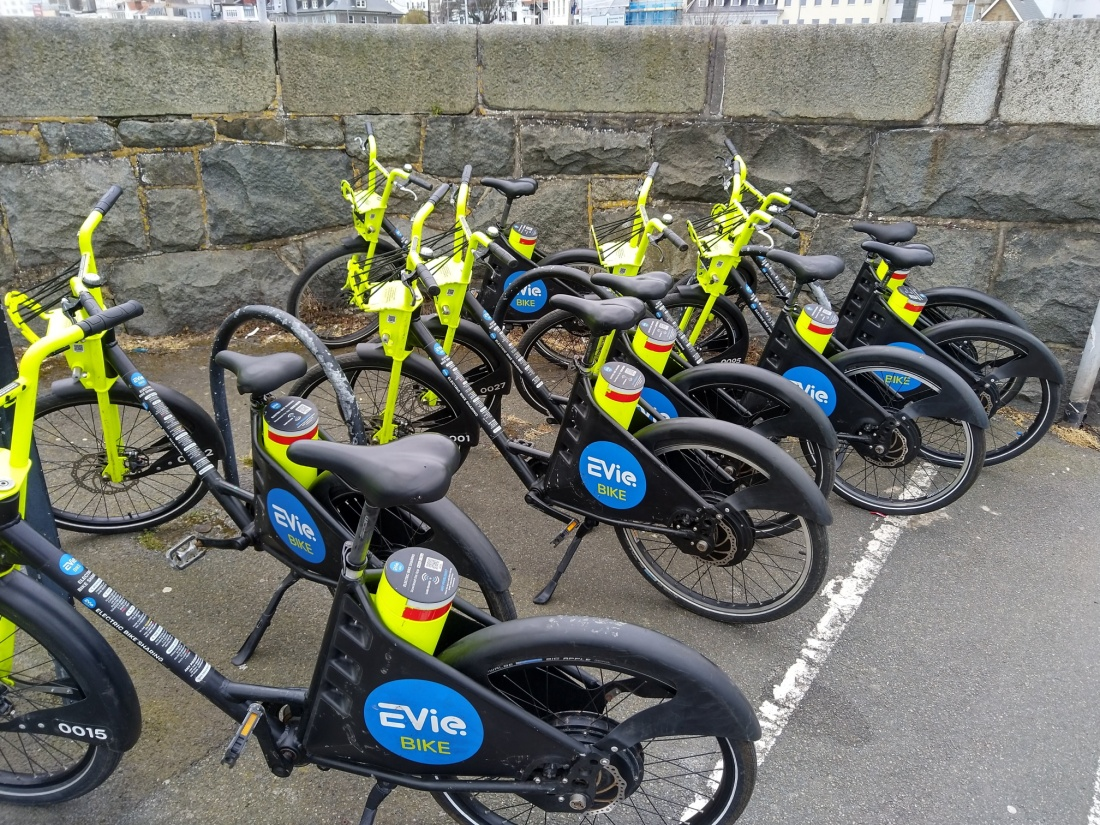 A collection of EVieBike branded electric bikes parked together at North Beach in Guernsey
